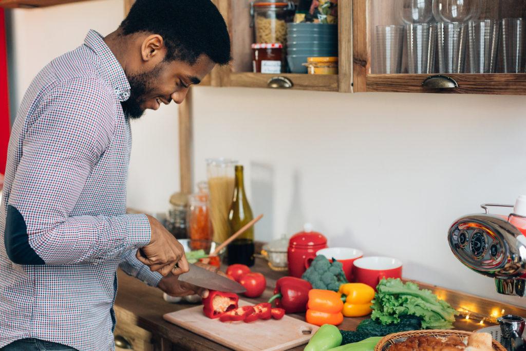 Man preparing delicious food in kitchen, cutting fresh vegetables