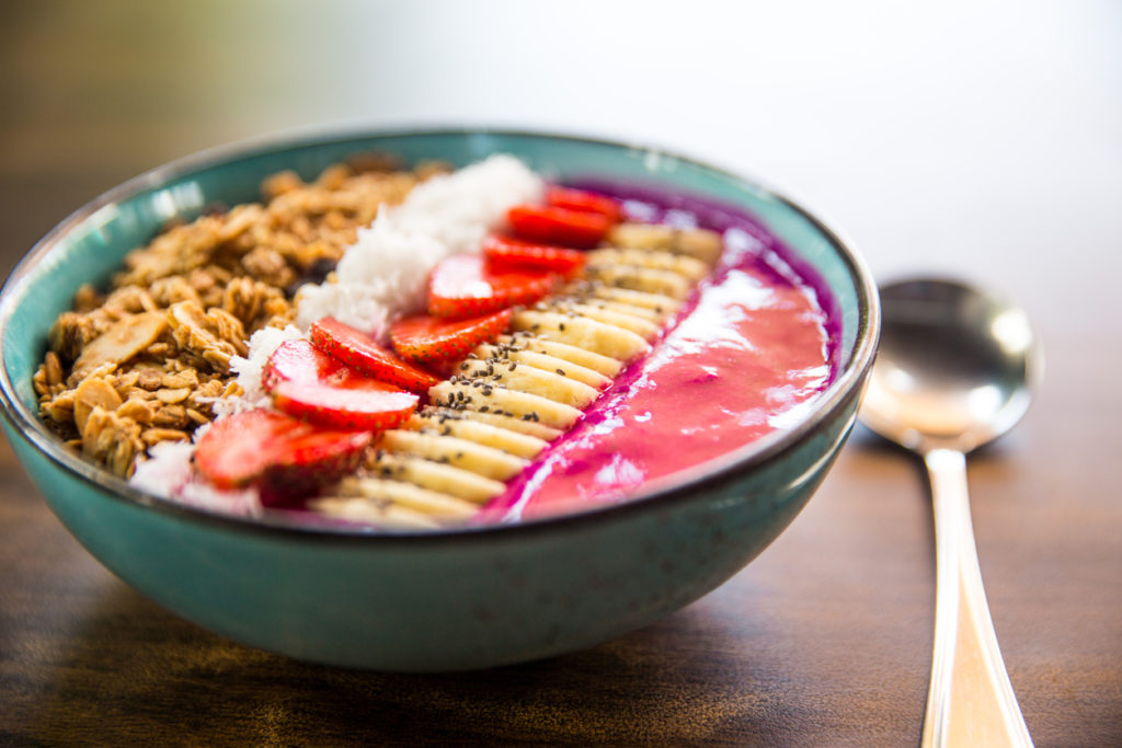 Smoothie bowl with strawberries, granola, chia seeds, and banana.